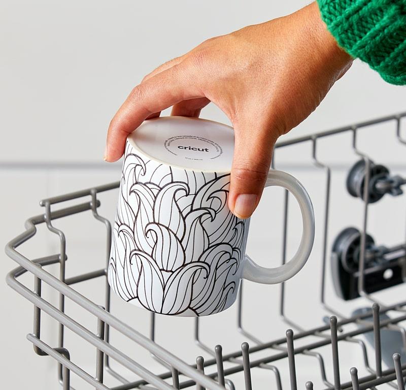 A hand placing a mug with a beard design inside the dishwasher rack