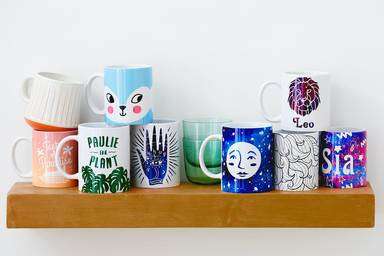 A variety of glasses and mugs setting on a kitchen shelf.