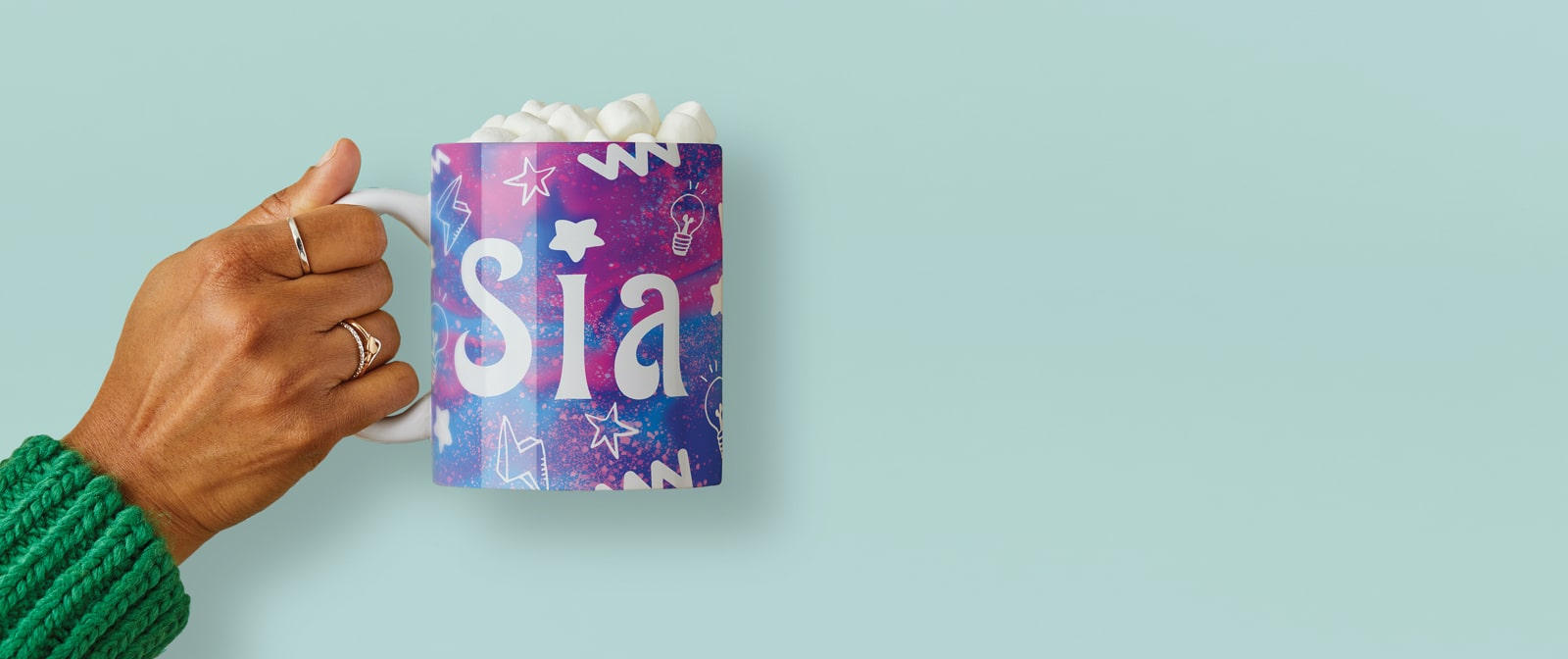 Hand holding a mug with the name Sia on it.