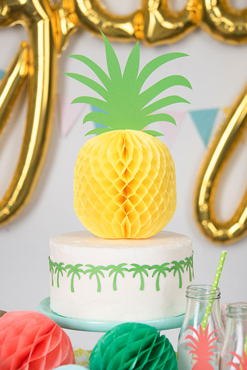Decorate a cake with cut shapes and a paper pineapple