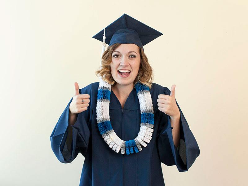 Happy graduate with lei